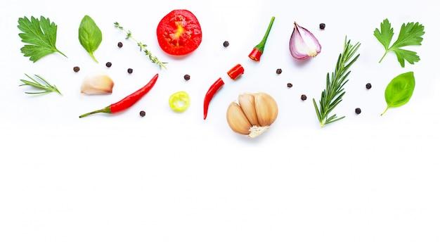 Vari ortaggi freschi ed erbe su bianco. concetto di mangiare sano Foto Premium