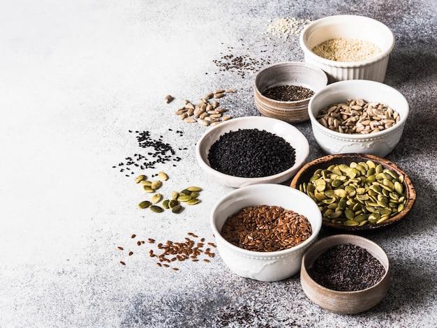 Vari semi - sesamo, semi di lino, semi di girasole, semi di zucca, papavero, chia in ciotole su uno sfondo grigio. Foto Premium
