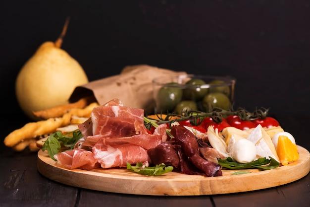Vari tipi di antipasti italiani: prosciutto, formaggio, grissini, olive, frutta Foto Premium