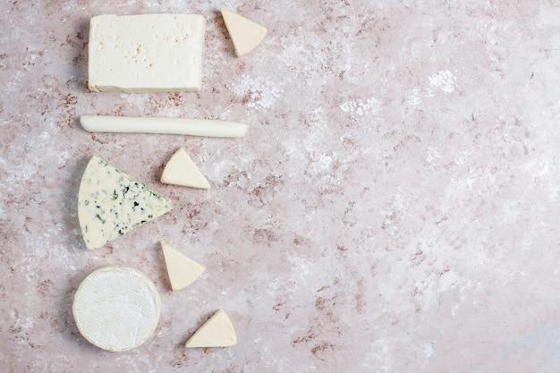 Vari tipi di formaggi su superficie marrone chiaro Foto Gratuite