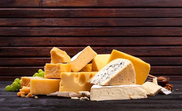 Vari tipi di formaggi sul tavolo in legno nero. Foto Premium