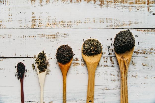 Varia tisana secca sul cucchiaio di legno sopra il tavolo Foto Gratuite