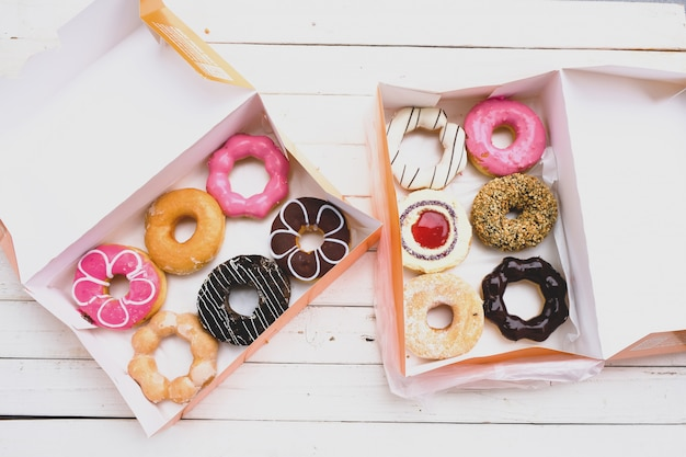 Varie ciambelle entrambi con un rivestimento bianco cioccolato-rosa, modello Foto Premium