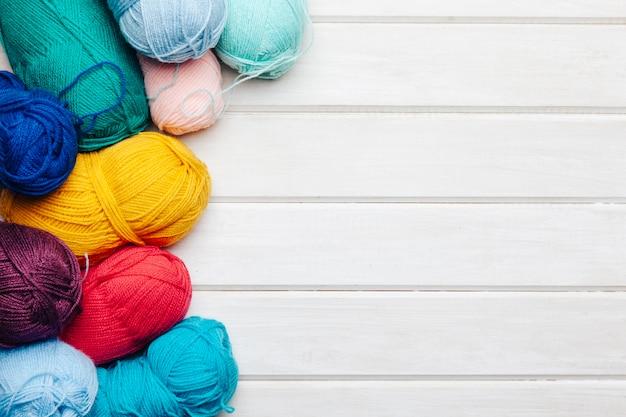 Varie palle di lana in diversi colori con spazio sulla destra Foto Gratuite
