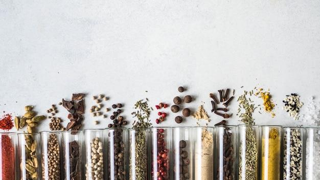 Varie spezie asciutte in tubi di vetro su fondo grigio. Foto Premium