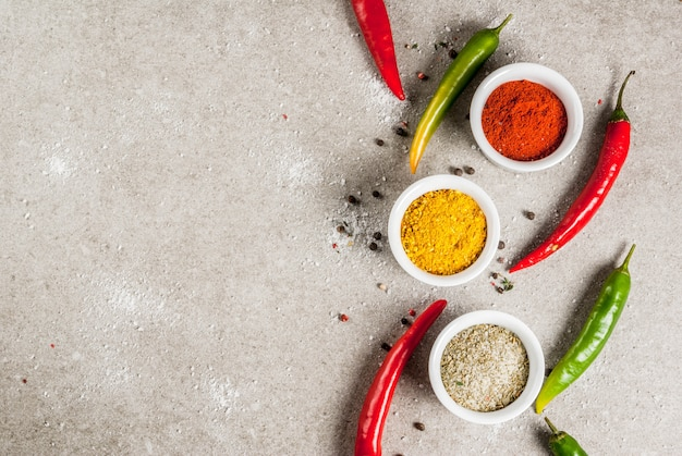 Varie spezie e condimenti. cucinando . curcuma, curry, paprika, pepe, peperoncino, basilico secco, sale, peperoncino fresco, timo. pietra grigia . vista dall'alto Foto Premium