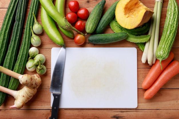 Varie verdure, spezie e ingredienti con un coltello Foto Premium