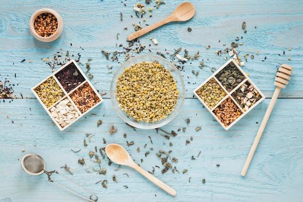 Varietà di erbe; cucchiaio; mestolo al miele; il colino del tè ed i fiori secchi del crisantemo cinese sistemano sulla tavola Foto Gratuite