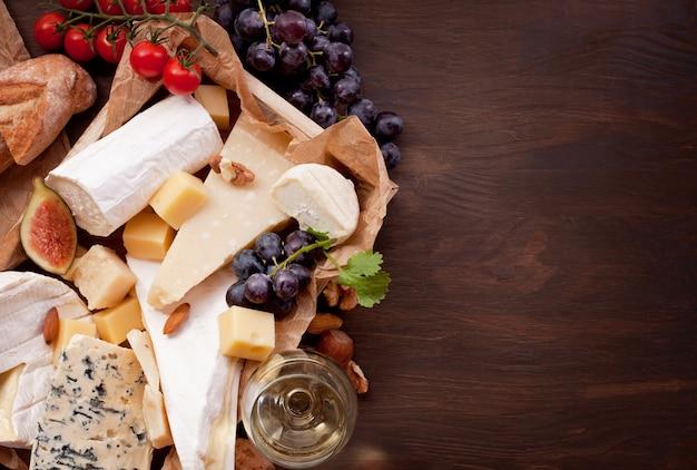 Varietà di formaggi diversi con vino, frutta e noci. Foto Premium