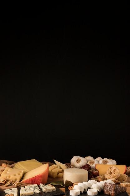 Varietà di formaggi su sfondo nero Foto Gratuite