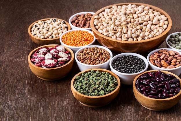 Vario assortimento di legumi indiani in ciotole su fondo in legno con copyspace. Foto Premium