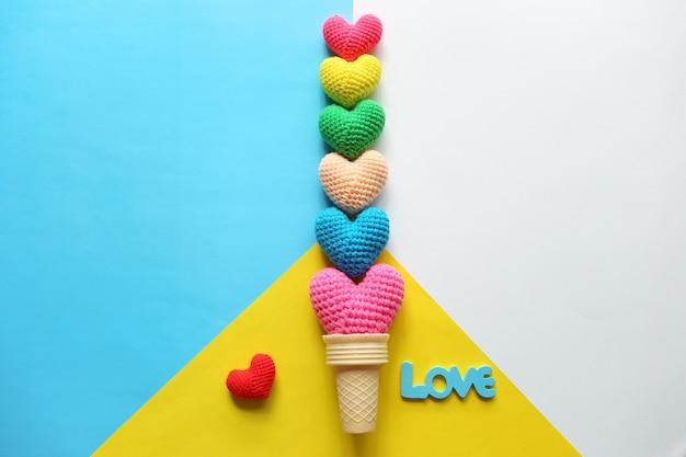 Variopinto del cuore fatto a mano all'uncinetto in tazza della cialda su fondo variopinto per il giorno di biglietti di s. valentino Foto Premium