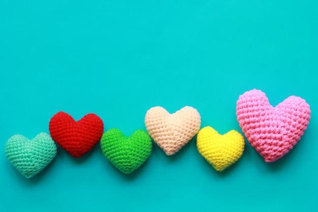 Variopinto del cuore fatto a mano all'uncinetto su fondo blu per il giorno di biglietti di s. valentino Foto Premium