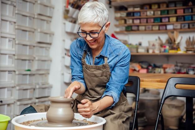 Vasaio femminile senior che lavora alla ruota delle terraglie mentre sedendosi nella sua officina Foto Premium