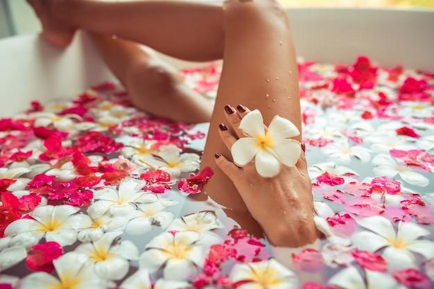 Vasca da bagno di lusso nella spa con le gambe nude di donna mostrando attraverso. Foto Premium