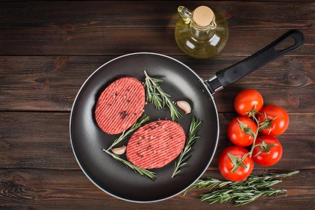 Vaschetta di costolette crude con rosmarino e aglio. fondo in legno marrone. Foto Premium