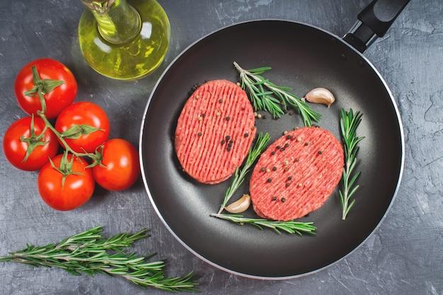 Vaschetta di costolette crude con rosmarino e aglio. sfondo di marmo grigio. Foto Premium