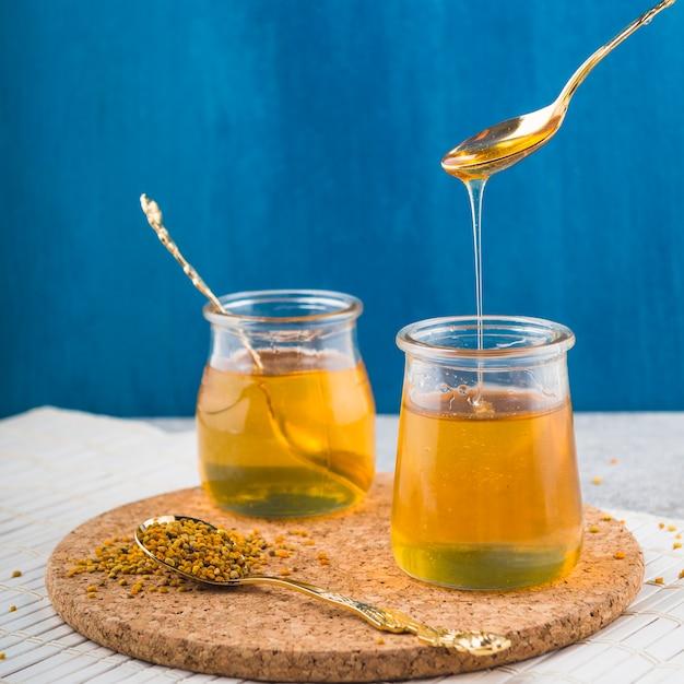 Vasetti di miele e cucchiaio con polline d'api su sottobicchiere di sughero Foto Gratuite