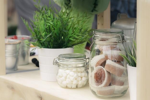 Vasetti di vetro con biscotti e muffin, piantine verdi in secchi decorativi in metallo. Foto Premium