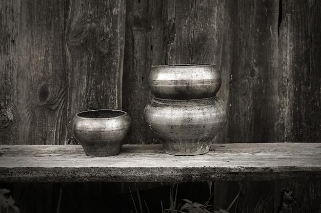 Vasi antichi per la cottura nella retro annata di stile rustico del fondo di legno scuro russo del forno Foto Premium
