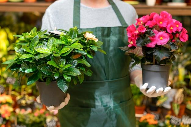 Vasi da fiori della tenuta dell'uomo di vista frontale con i fiori Foto Gratuite