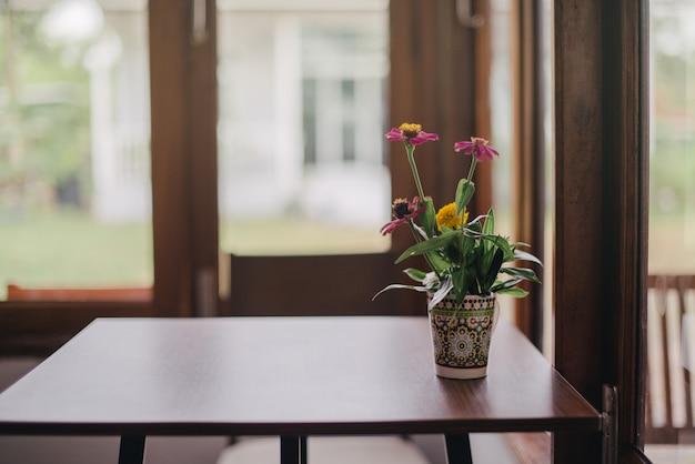 Vasi da fiori messi vicino alla finestra in una caffetteria vintage Foto Premium
