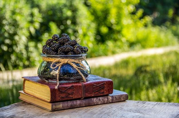Vaso con bacche estive e pila di libri. Foto Premium
