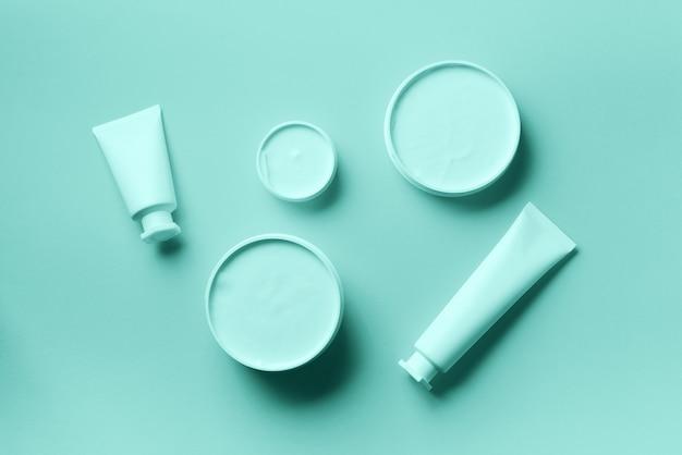 Vaso cosmetico bianco, tubo, bottiglia e foglia di monstera tropicale Foto Premium