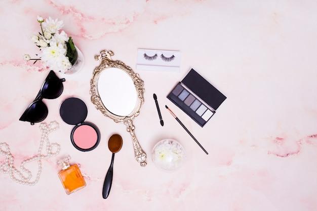 Vaso di fiori; occhiali da sole; collana; specchietto; cipria compatta; pennello da trucco; tavolozza di ombretti e ciglia su sfondo rosa Foto Gratuite