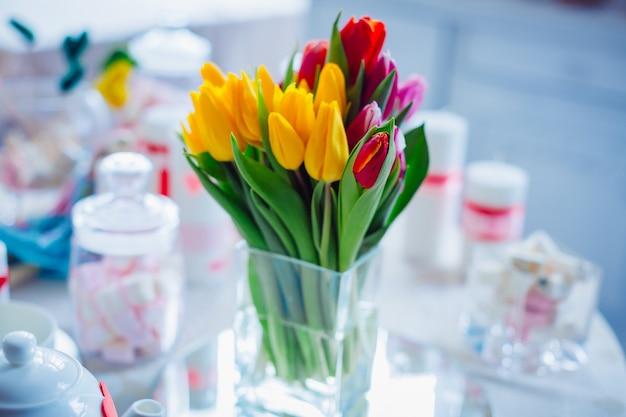 Vaso di vetro con bouquet di tulipani rossi, gialli e rosa Foto Premium