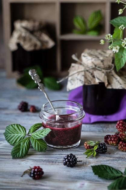 Vaso di vetro con il primo piano di salsa blackberry. ramo con bacche e foglie in una scatola di legno intagliato su un legno scuro Foto Premium
