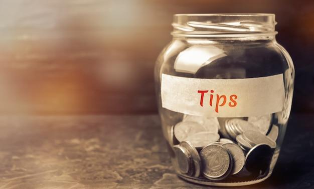 Vaso di vetro con monete e punte di iscrizione Foto Premium