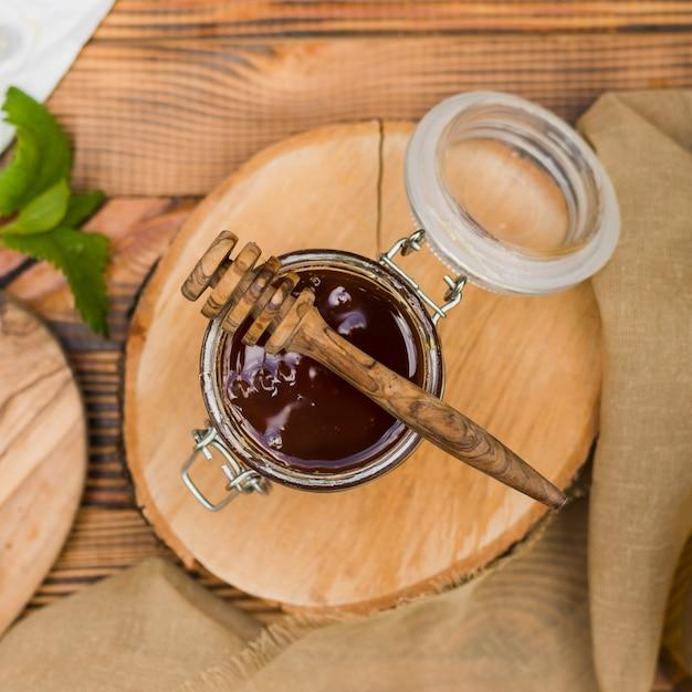 Vaso di vetro con vista dall'alto pieno di miele con cucchiaio di miele Foto Gratuite