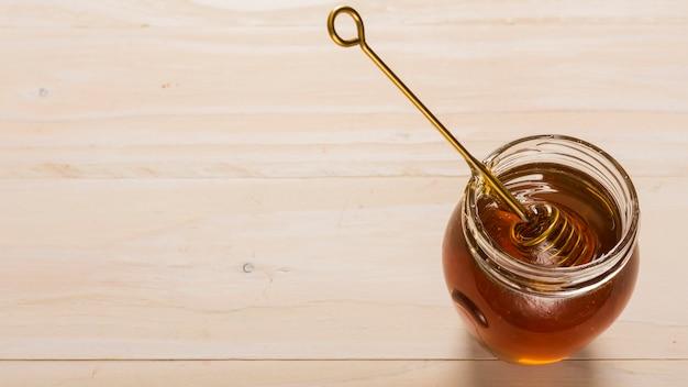 Vaso di vetro con vista dall'alto pieno di miele Foto Gratuite