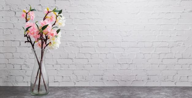 Vaso di vetro del fiore di ciliegia secco sul muro di mattoni bianco t Foto Premium