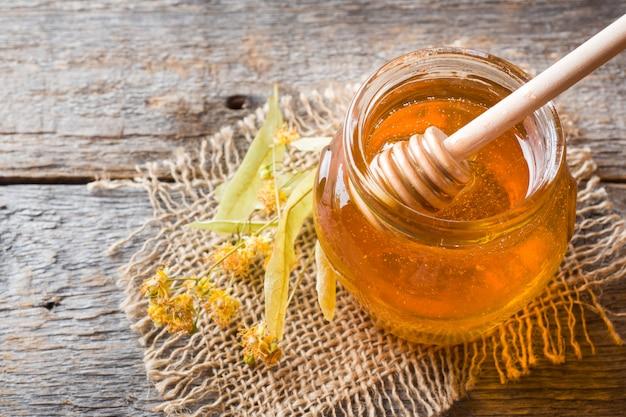 Vaso di vetro di miele, fiori di tiglio su superficie di legno Foto Premium