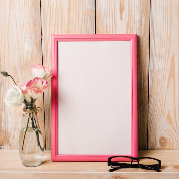 Vaso e occhiali vicino alla cornice bianca sulla scrivania Foto Gratuite