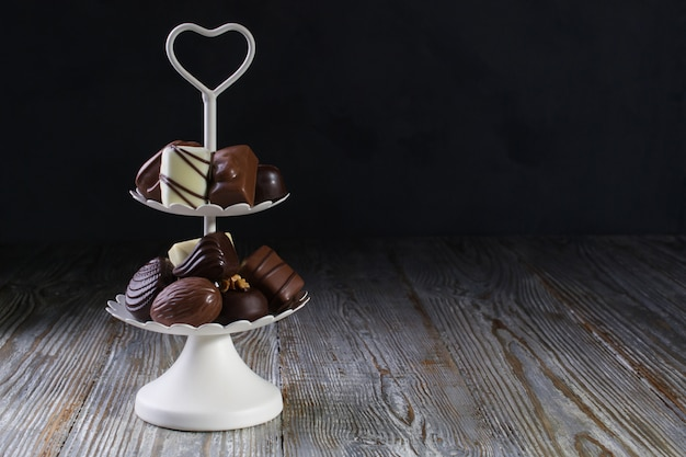 Vassoio bianco a due piani pieno di dolciumi con caramelle al cioccolato e praline. copia spazio Foto Premium