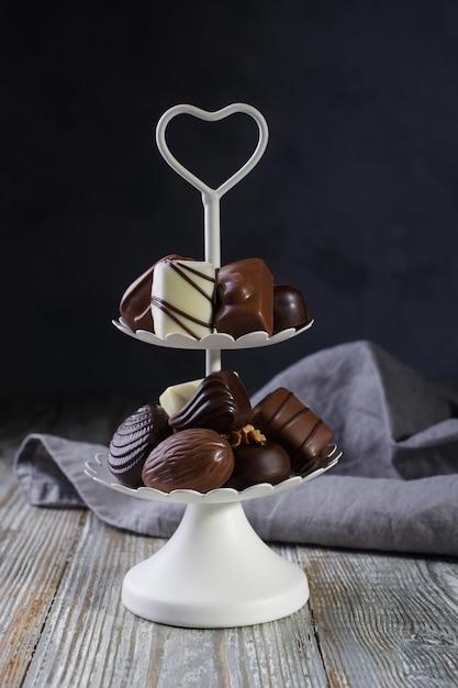 Vassoio bianco a due piani pieno di dolciumi con caramelle al cioccolato e praline Foto Premium
