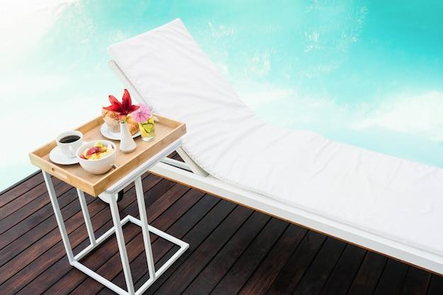 Vassoio con colazione nel tavolino e lettino vicino alla piscina Foto Premium