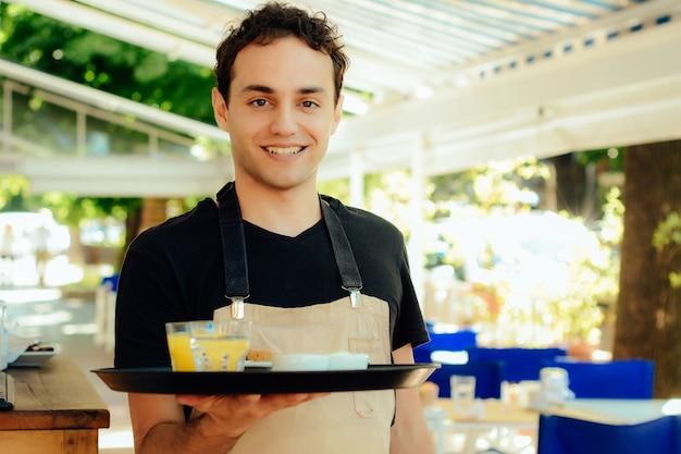 Vassoio di detenzione giovane cameriere. Foto Premium