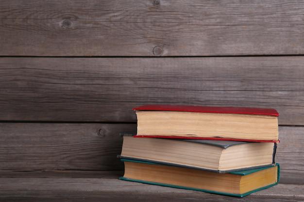Vecchi libri d'annata sulla tavola di legno grigia Foto Premium