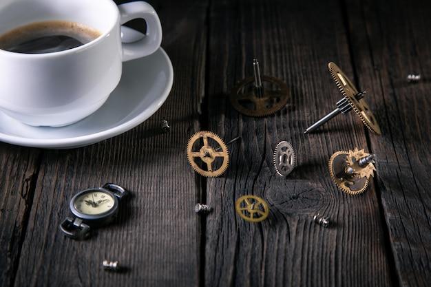 Vecchi orologi, ingranaggi, viti, una tazza di caffè incompiuto su assi di legno. Foto Premium
