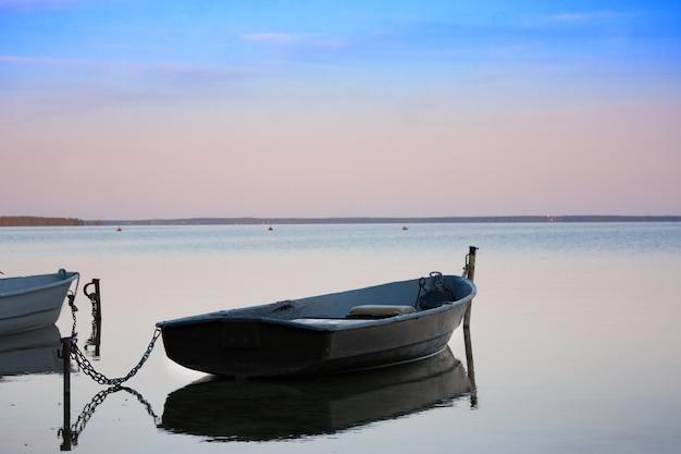 Vecchi pescherecci con catena sul lago al tramonto Foto Premium