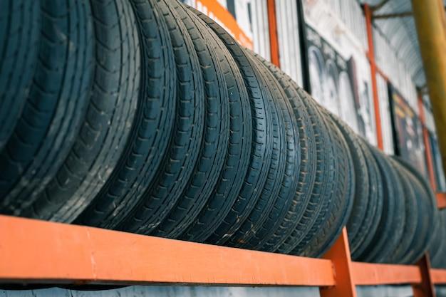 Vecchi pneumatici che sono allineati sul supporto per pneumatici Foto Premium
