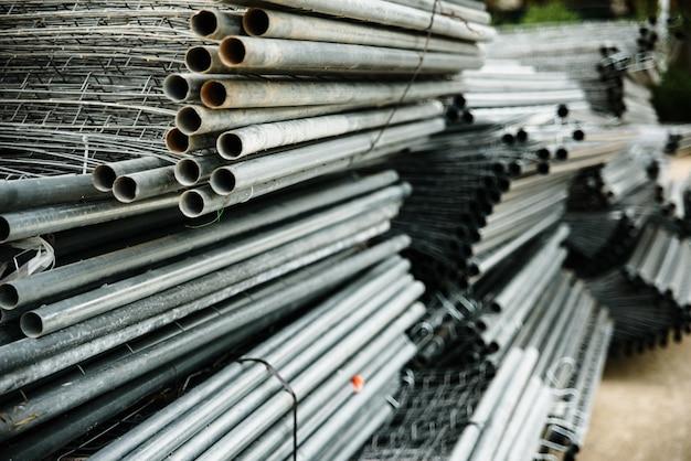 Vecchi tubi d'acciaio impilati in un magazzino industriale. Foto Premium