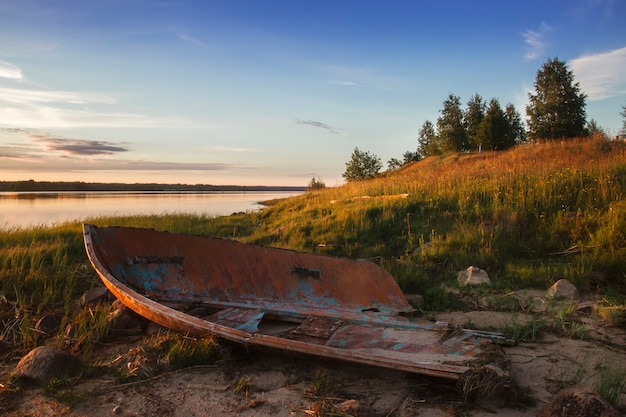 Vecchia barca rotta sulla riva del lago al tramonto Foto Premium