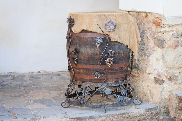 Vecchia botte di vino di quercia con anelli di ferro e uva sul muro antico di pietra. Foto Premium
