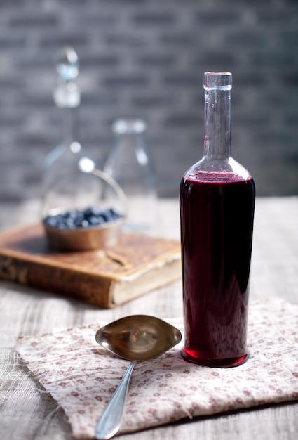 Vecchia bottiglia di vino con aceto di bacche fatto in casa. Foto Premium