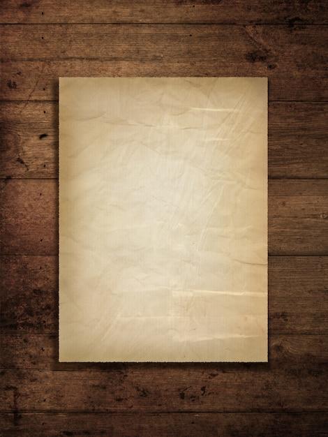 Vecchia carta macchiata su una priorità bassa di legno del grunge Foto Gratuite